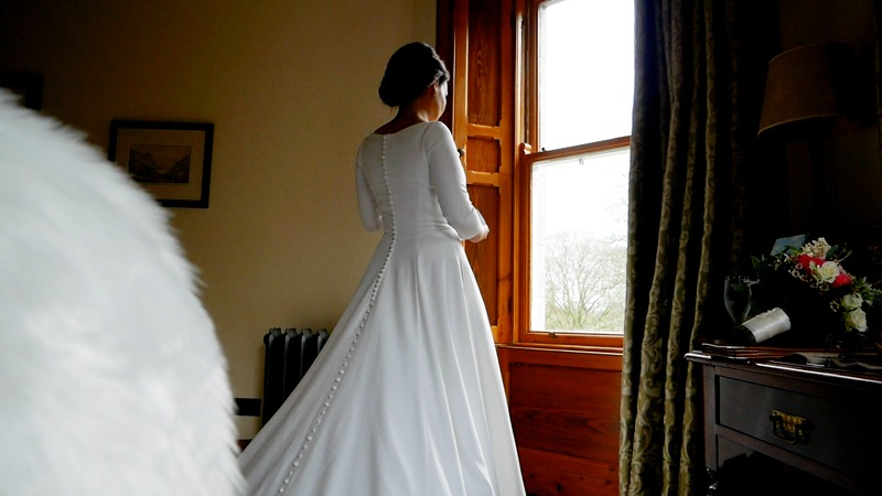 wedding-videographer-filming-bride-looking-out-bridal-suite-window